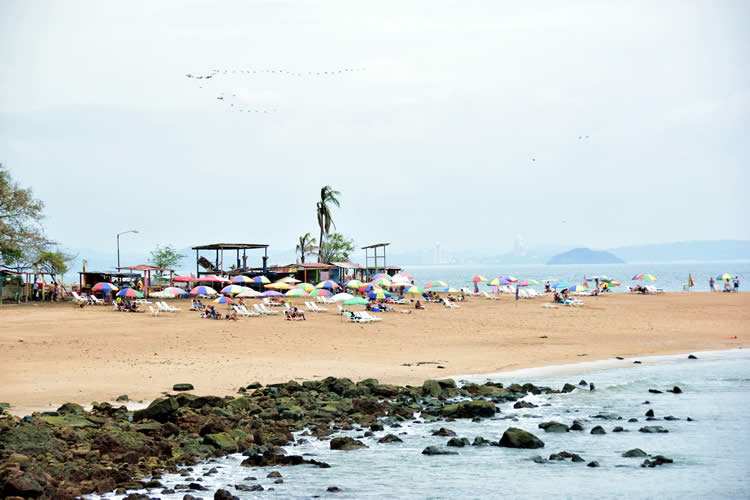 Taboga's beach with tourists under umbrellas and sunbathing