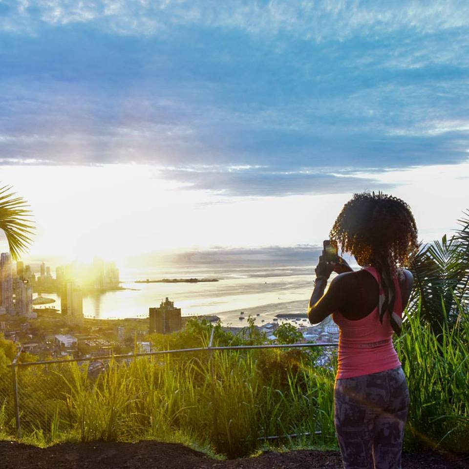 Tourist taking photo with smartphone of Panama City from Ancon Hill at Sunrise