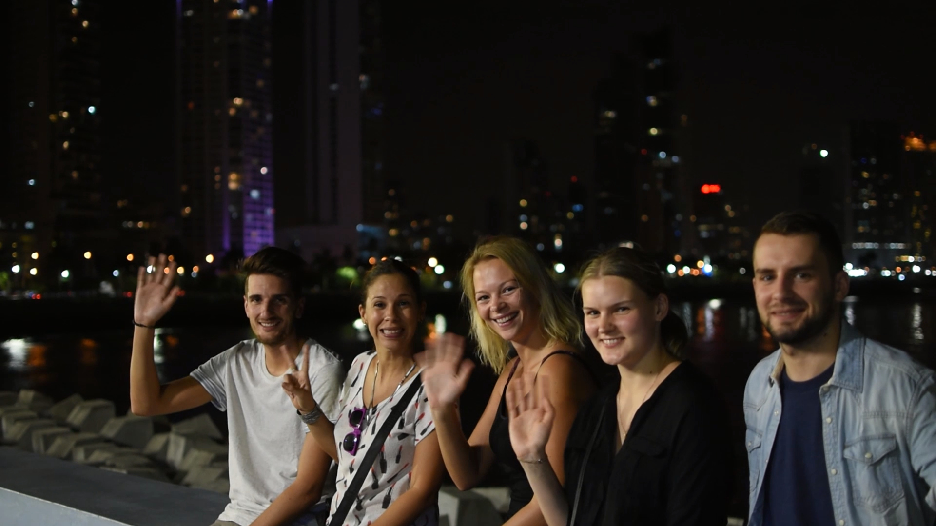 Habla Ya students hanging out in Panama City in the evening with the skyline and lights in the back