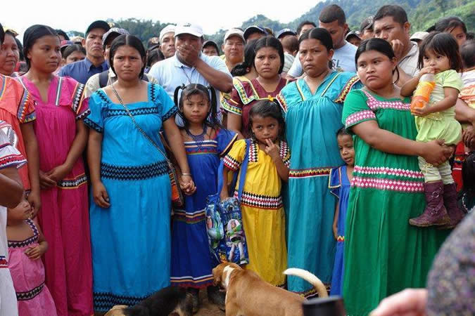 Ngäbe men typically wear homemade bell bottom pants, straw hats and rubber boots, while women wear full bright colored dresses with shoulder and neckline adornments and embroidered bands around the waist and bottom; these are called naguas. Women generally do not wear shoes. These items are usually made at home with hand crank sewing machines and, like chacaras, sold for extra income.