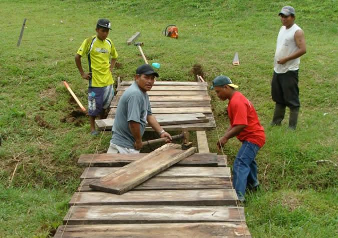 Community pitches together to build a bridge over a stream in a busy section of the village. The men do the building…