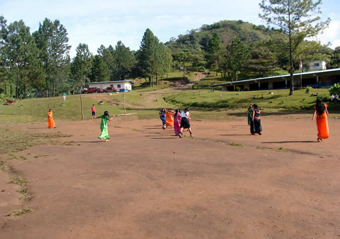 Playing soccer on the school's field.
