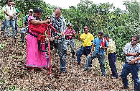 Government worker showing Ngäbe women how to operate a tool